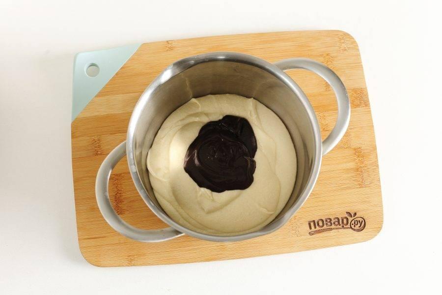 Разделите тесто на 2 части. В одну добавьте шоколадную пасту.