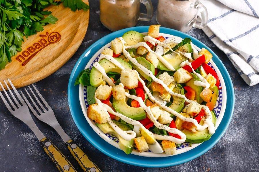 Украсьте блюдо майонезом, посолите его и поперчите. Сразу же подайте к столу, пока мякоть авокадо не потемнела.