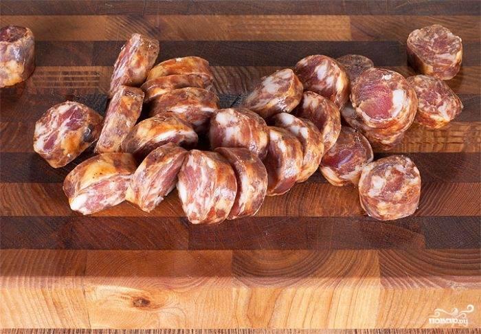 Копченую колбасу нарезать ломтиками любимой толщины и поджарить с двух сторон на сковороде без масла или гриле.