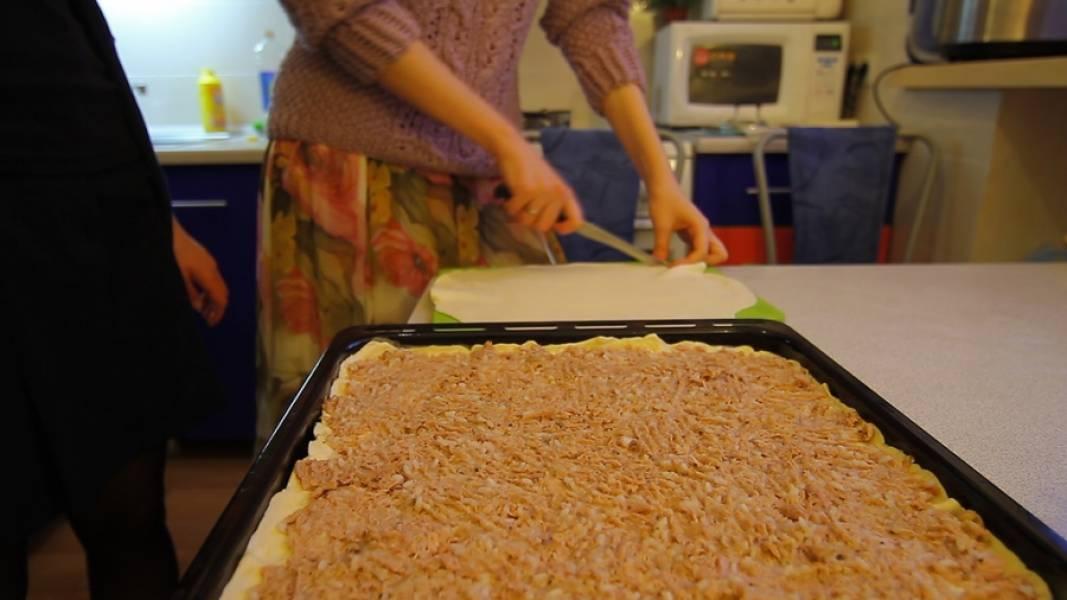 Смешиваем рыбную консерву, отваренный до готовности рис и мелко нарезанный лук. Солим, перчим, добавляем специи. Получившуюся начинку равномерно распределяем по тесту.