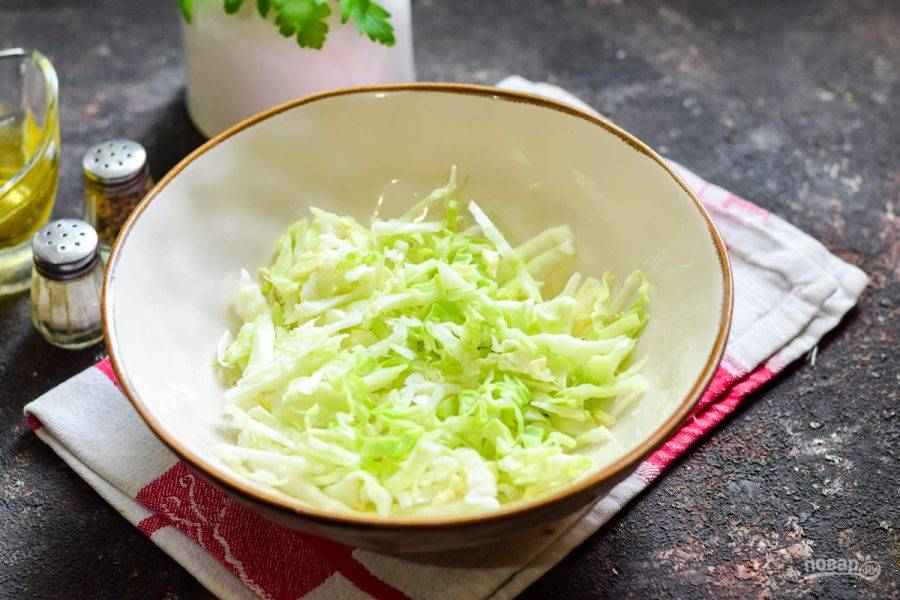 Молодую капусту нашинкуйте тонкими полосками. Переложите капусту в салатник.