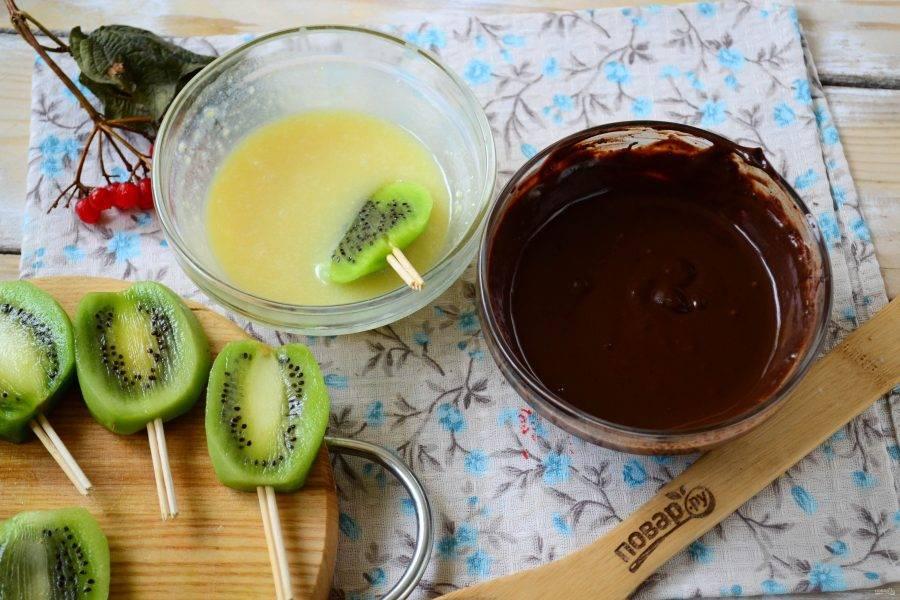 Обмакните киви на палочке сначала в белый шоколад, а затем в черный, как показано на фото.