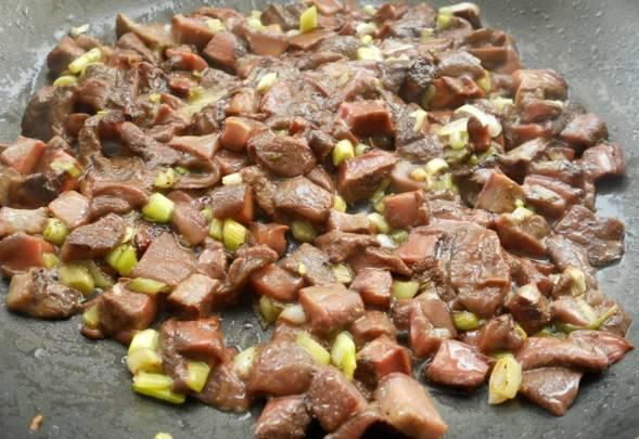 Шампиньоны промойте и нарежьте небольшими пластинками. Обжарьте грибы с измельченным зеленым луком на растительном масле. Соль и перец по вкусу.