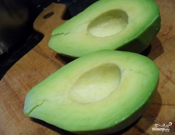 Авокадо помойте. Очистите его от кожуры, достаньте из него косточку.