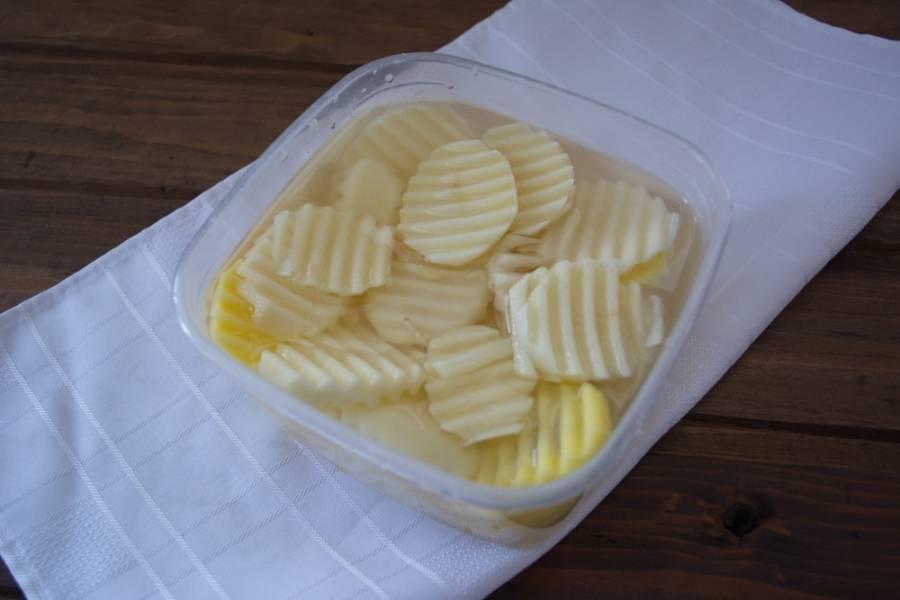 Картофель нужно очистить от шкурки и нарезать фигурно. Можно и просто нарезать тонкими кружочками, но фигурная нарезка в готовом блюде смотрится солиднее. Картофель залейте водой и отставьте.