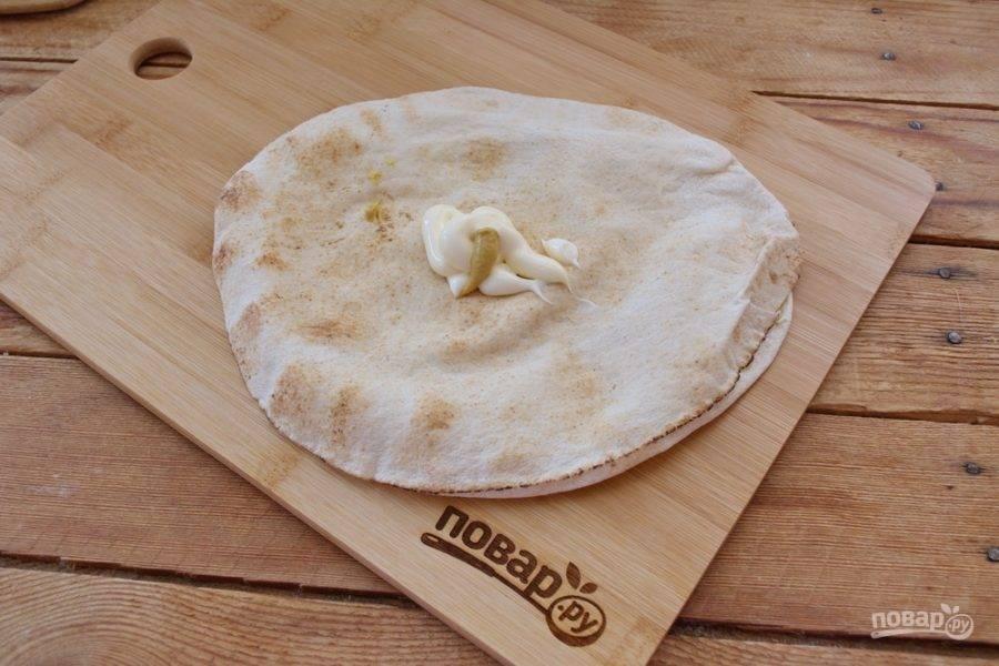 Майонез смешайте с горчицей и смажьте одну сторону питы. Это можно сделать непосредственно на пите, не пачкая тарелок.