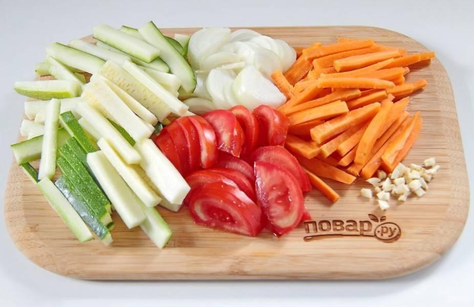 Тем временем нарежьте овощи. Кабачок и морковь - брусочками, помидоры - дольками, лук - перьями, чеснок - порубите ножом.