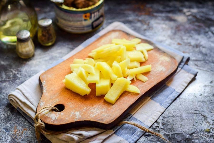 Очистите картофель, вымойте и просушите. Нарежьте картофель крупными брусками и переложите в кастрюлю. Влейте в кастрюлю воду - 1,3 литра, после чего отправьте варится картофель на огонь - 15-20 минут.