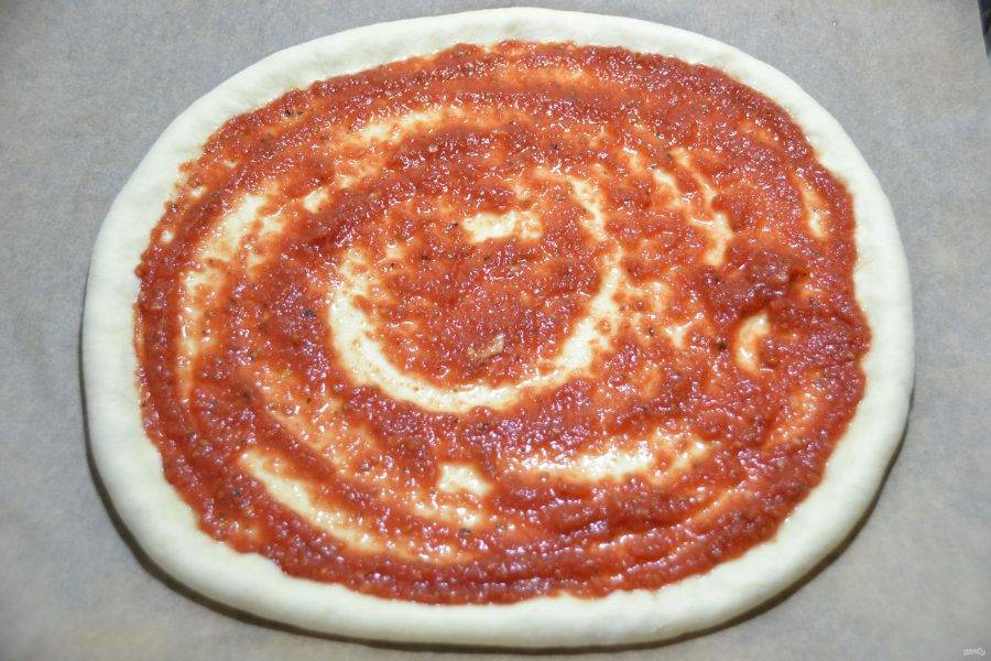 Нанесите на лепешку томатный соус и отправьте в духовку, разогретую до 180-200 градусов на 8 минут.