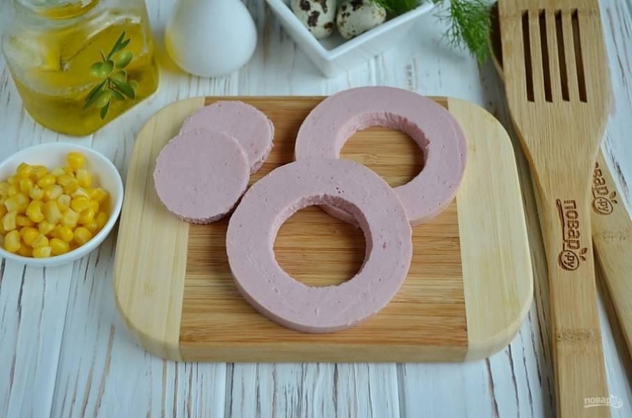Отрежьте два кружочка колбасы. В центре рюмочкой выдавите часть колбасы. Из этих серединок я вырезала сердечки, это легко сделать острым ножом или формочкой для печенья.