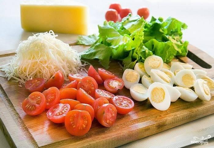 Сыр натрите на терке, помидоры черри и яйца отварные порежьте на половинки.