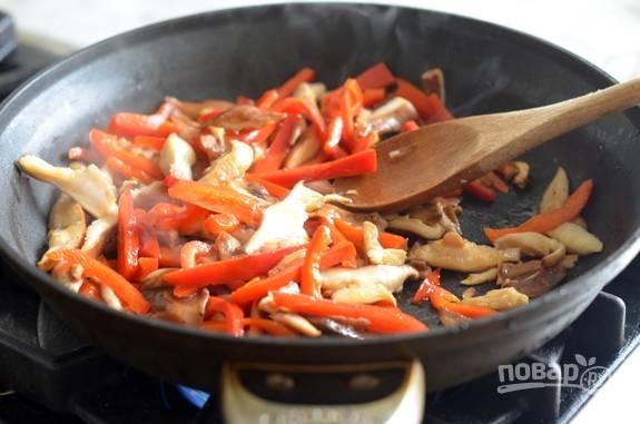 Нарежьте брусками перец и грибы. В сковороде разогрейте масло. Обжарьте грибы и перец в течение 5 минут, помешивая, на сильном огне.