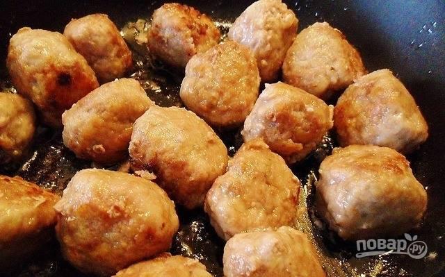 В сковороду налейте растительное масло и поставьте ее на плиту разогреваться. Выложите в сковороду биточки в муке и обжаривайте их до коричневой корочки со всех сторон на среднем огне в масле.