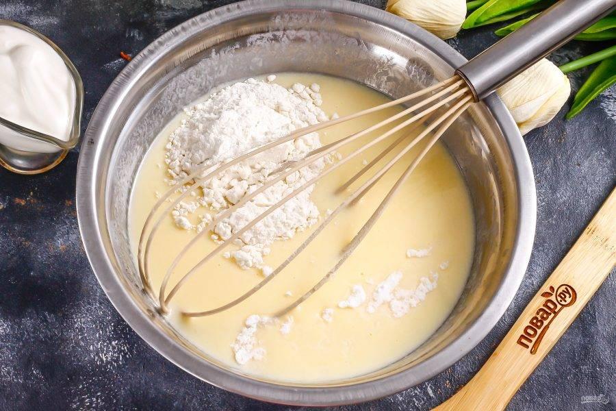 Всыпьте муку и разрыхлитель. Аккуратно вмешайте сухие ингредиенты в жидкую массу, но не взбивайте. Тесто должно получиться очень густым, плотным, как густая сметана.