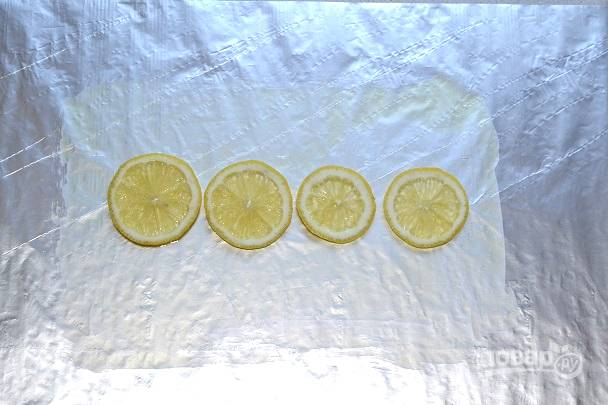 Лист фольги смажьте небольшим количеством масла и выложите в центр лимоны.