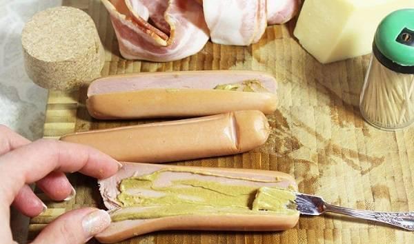2. Первым делом нужно очистить сосиски от пленки и надрезать аккуратно, но не до конца. Смазать соусом по вкусу. При желании можно добавить немного перца, измельченного чеснока или других специй по вкусу.