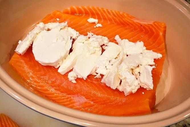 2. Сверху выложите сливочный сыр. Использовать в рецепте приготовления семги со сливочным сыром можно любой сыр, который вам больше по вкусу. Отлично подойдет также сыр с зеленью. Или его можно предварительно соединить с измельченной свежей зеленью и выложить на рыбку.
