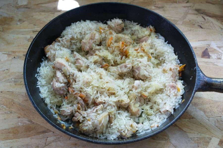 6. К мясу с овощами добавляем сухой сырой рис. Даем рису пропитаться маслом и соком курицы.