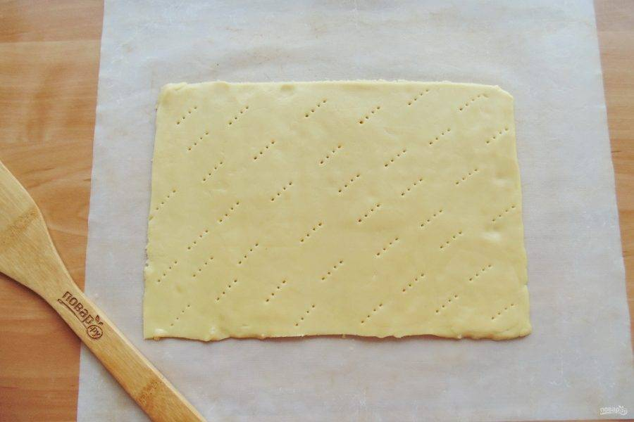 Достаньте тесто из холодильника и раскатайте в пласт толщиной 3-4 мм. Наколите вилкой и отправьте в духовку, разогретую до 175-180 градусов.