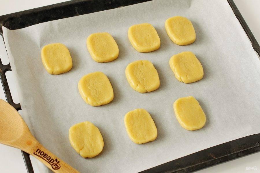 Переложите каждый кусочек на противень застеленный пергаментом. Сверху прижмите печенье руками, добиваясь нужной толщины. Чем толще печенье, тем оно мягче, чем тоньше, тем получается хрустящее. Выпекайте в духовке при температуре 180 градусов около 15 минут.