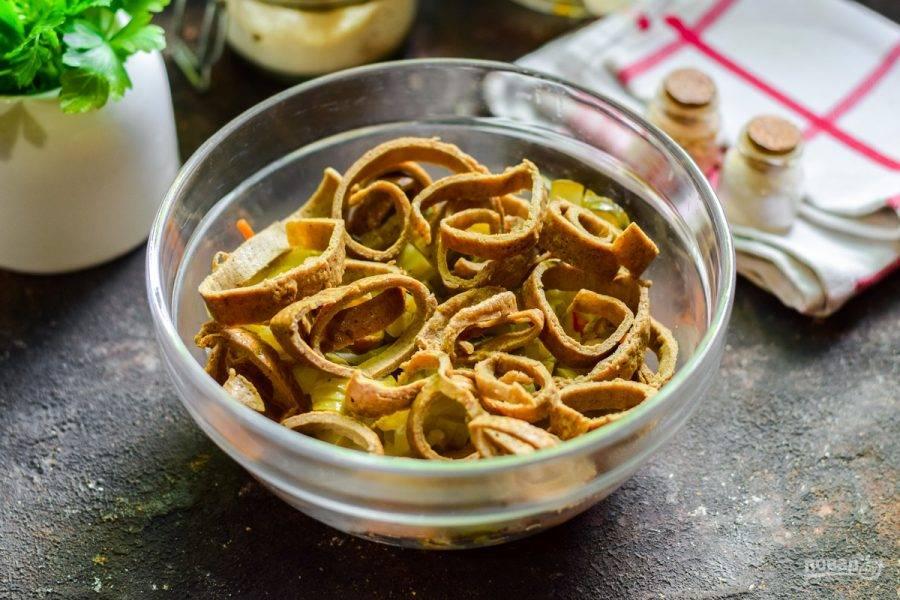 Печеночные блины сверните рулетиками и нарежьте соломкой, переложите в салат.