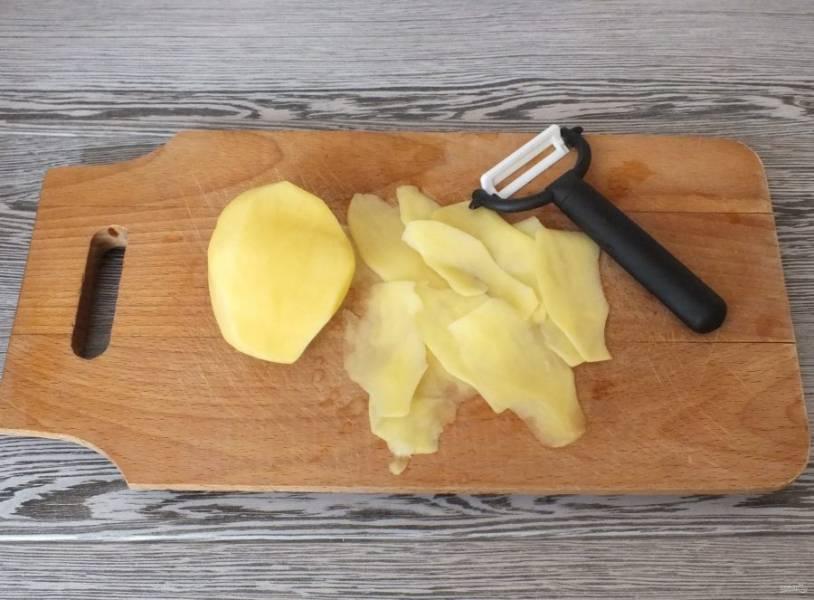 Подготовленный картофель нарежьте с помощью картофелечистки, тонкими ломтиками.
