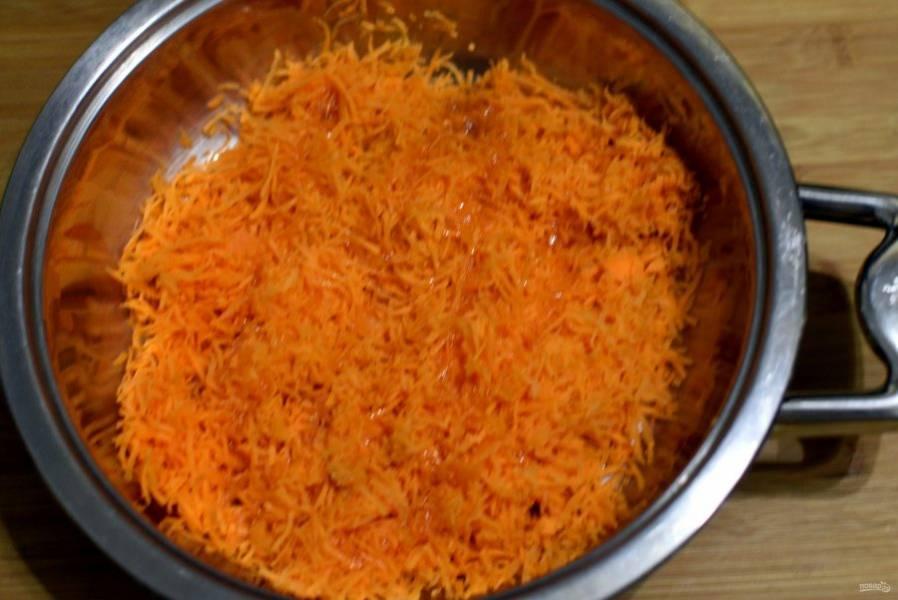 В сотейник выложите половину сахара, добавьте ложку воды и проварите до начала карамелизации. Влейте половину масла, перемешайте и добавьте тертую на мелкой терке морковь. Хорошо перемешайте и потушите пару минут. Остудите.