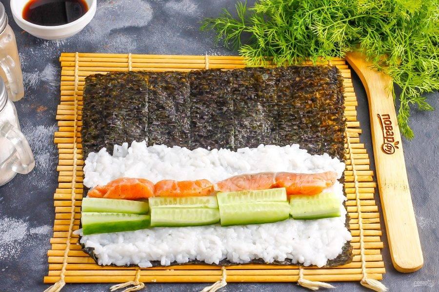 Выложите сливочный сыр, а на него — ломтики слабосоленой рыбы. Промойте огурец и срежьте хвостики, нарежьте длинными брусочками. Выложите на рыбу.
