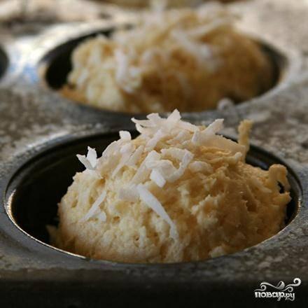 3. Равномерно разделить тесто между отделениями подготовленной формы. Посыпать сверху каждый маффин примерно 1 чайной ложкой оставшейся кокосовой стружки.