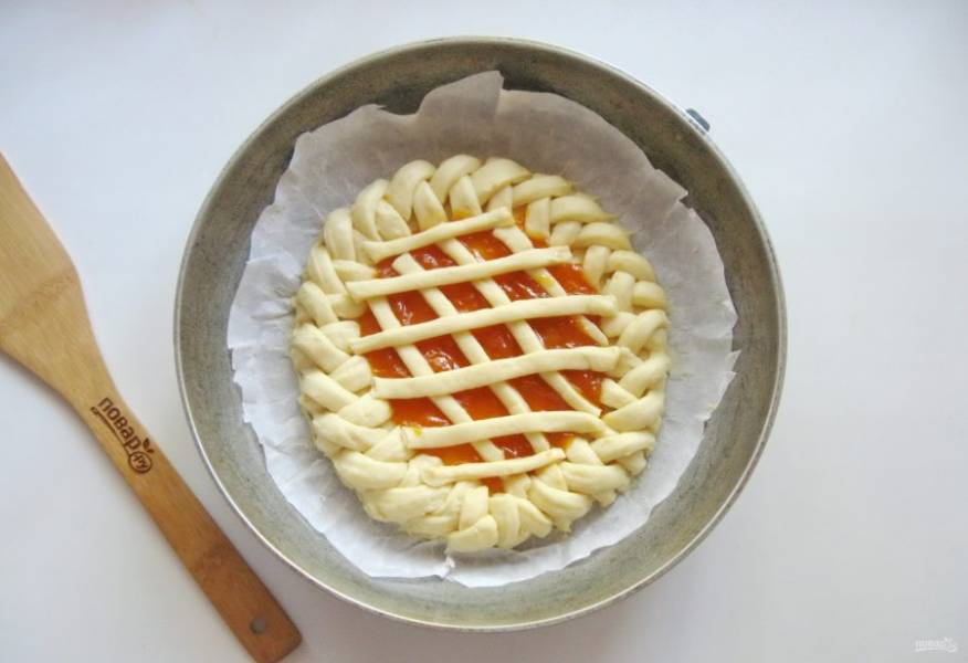 Из меньшей части теста сделайте полоски, которые выложите на пирог решеткой. Поставьте пирог в теплое место на 25-30 минут. Затем смажьте желтком и отправьте в духовку.