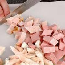 Куриное филе промыть, варить в подсоленной воде 10–12 минут, пока не приготовится. После моментально окунуть в ледяную воду, чтобы курица не переварилась и не стала жесткой. Бульон оставить. Как филе остынет, порезать его на средние кубики. Колбасу и карбонад нарезать примерно так же. Перемешать все виды мясной нарезки, Переложить ее в холодильник.