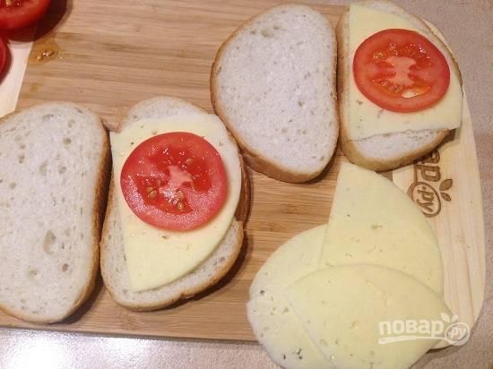 4. На ломтик хлеба выкладываем тонкий ломтик сыра, поверх него выкладываем кружок помидора.