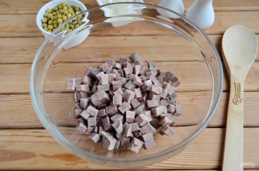 Порежьте язык крупными кубиками, сложите его в салатник.