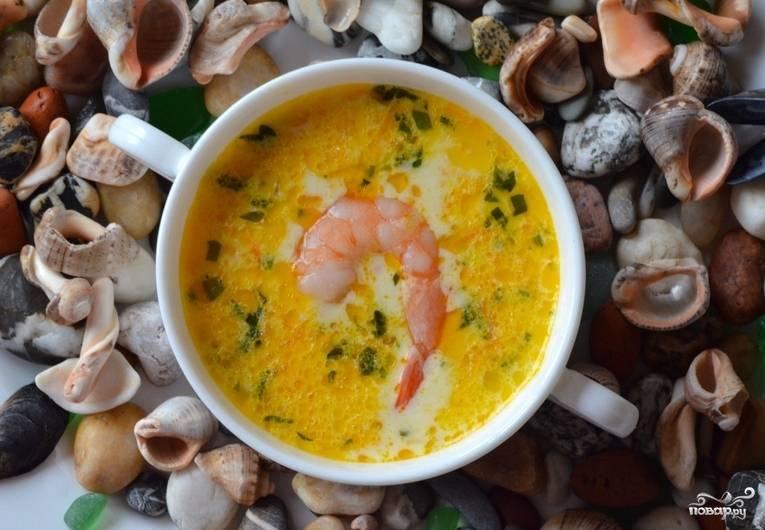 Теперь всыпьте креветки, измельченный чеснок и нарезанную зелень. Как только суп закипит, выключайте его. Дайте настояться 15 минут. Потом подавайте, украсив креветками с хвостиком.