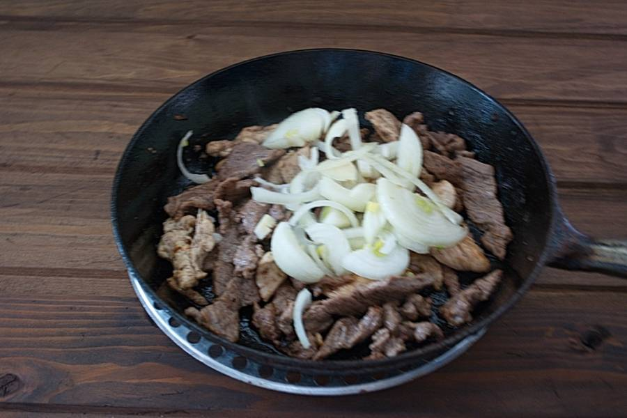 На  сковороду к мясу выкладываем нарезанный лук.