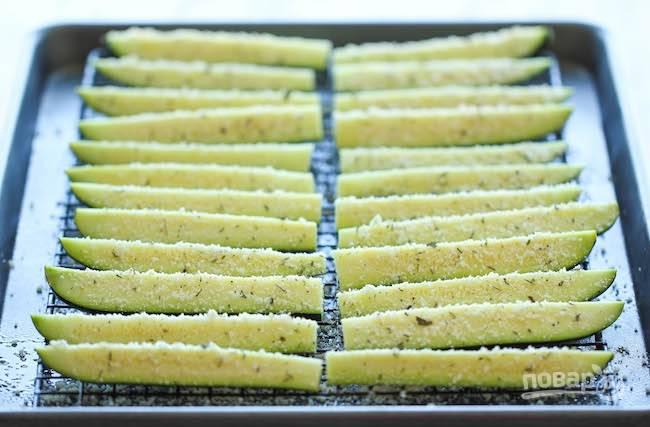 Молодые кабачки или цуккини нарежьте вдоль на 4 части или 8 частей в зависимости от размера плодов. Выложите на противень, сбрызните маслом и посыпьте смесью приправ.
