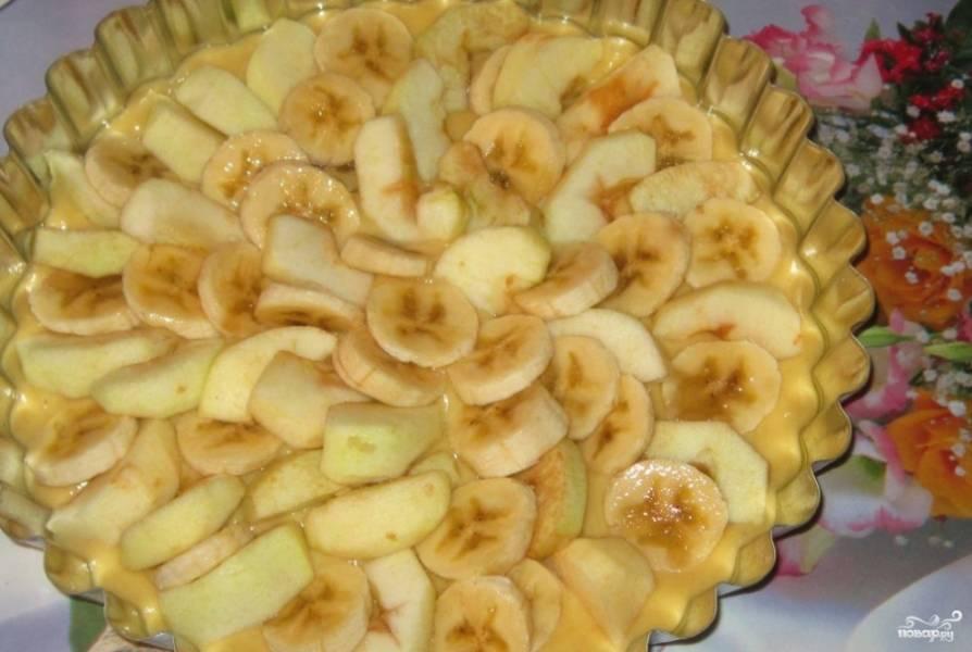 Разогрейте духовку до 180 градусов. Форму для выпечки смажьте растопленным маслом. Выложите тесто, а сверху уложите яблоки и бананы.