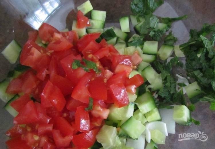 2.Нарежьте кубиками огурцы и помидоры, измельчите мяту и зеленый лук. Выложите все овощи и зелень в миску.