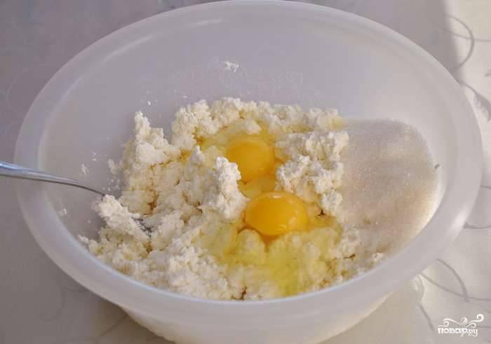 Творог выкладываем в посуду и разминаем хорошенько. Всыпаем сахар, манную крупу и разбиваем яйца. Перемешиваем массу.