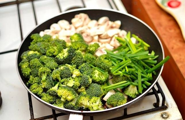 Выкладываем овощи: зеленый лук, брокколи и грибы. Обжариваем минуту, не перемешивая.