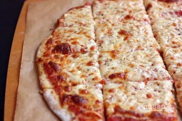 5.Достаньте пиццу и сразу разрежьте на кусочки, подавайте к столу, пока она еще горячая.