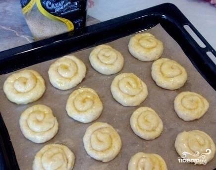 Отщипывайте от теста кусочки и формируйте из них булочки, раскатывая тесто в жгут а потом скатывая улиточкой. Выложите булочки на застеленный пергаментом противень. Смажьте их сырым желтком и присыпьте сахаром. Выпекайте булки при 180 градусах 50 минут.