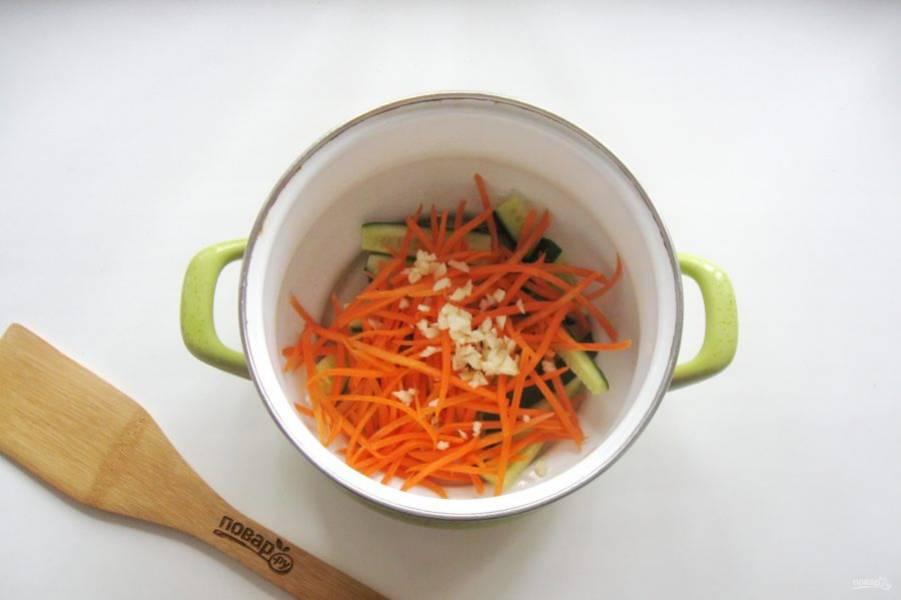 Огурцы и морковь выложите в кастрюлю. Добавьте измельченный чеснок.