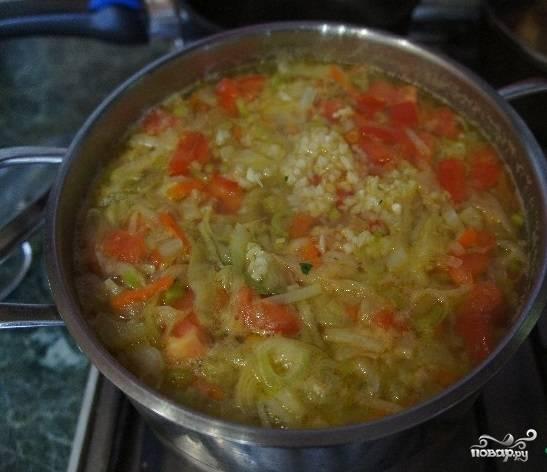 7. На завершающем этапе добавьте в кастрюлю порей, помидоры. Положите парочку лавровых листиков. Продолжайте варить, но недолго (5-7 мин.). После того, как выключите огонь, положите мелко нарубленный чеснок и накройте крышкой. Суп настоится приблизительно через 10 минут.