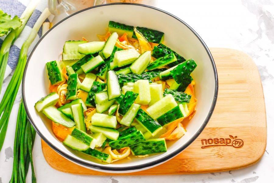 Промойте свежие огурцы, срежьте хвостики с овощей и нарежьте их брусочками. Добавьте в емкость к яичной нарезке.