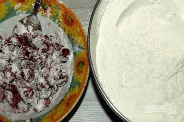Заранее разморозьте вишню и дайте стечь лишней жидкости. Пшеничную муку просейте вместе с разрыхлителем, добавьте соль и перемешайте сухие ингредиенты. В подготовленную вишню добавьте 2 ст. л. мучной смеси и перемешайте.
