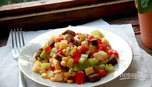 4.В миску выкладываю перец и кукурузу, твердый сыр и сухарики (предварительно убираю чеснок), заправляю оливковым маслом и перемешиваю.