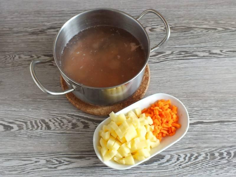 В рыбный бульон добавьте рыбу без косточек, нарезанные мелким кубиком картофель и морковь. Поставьте на огонь. Варите до готовности овощей.