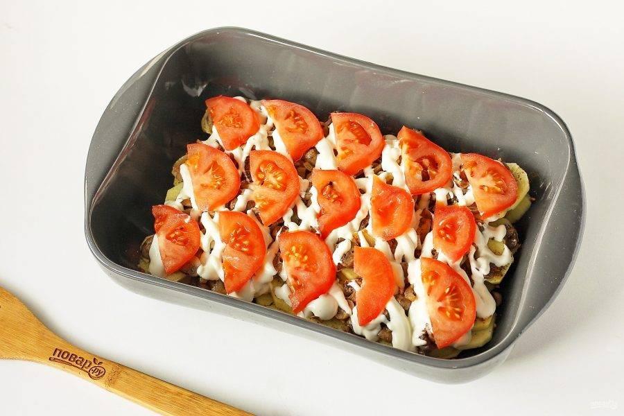 Смажьте слой майонезом и выложите нарезанный дольками помидор. Посолите слой, поперчите по вкусу, накройте форму фольгой и запекайте в духовке при температуре 180 градусов около 40 минут. Затем фольгу уберите, посыпьте верх тертым сыром и готовьте еще 15-20 минут. Ориентируйтесь по готовности картофеля.