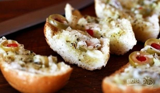 Запекайте хлеб с сыром в духовке в течение 10 минут. Подавайте закуску, нарезав её кусочками. Приятного аппетита!